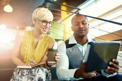 Due piccoli imprenditori millenial creativi che lavorano alla strategia sociale di media facendo uso di una compressa digitale me Immagini Stock