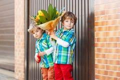 Due piccoli ragazzi adorabili felici del fratello germano con la fioritura fiorisce Fotografia Stock Libera da Diritti