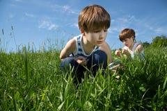 Due piccoli ragazzi curiosi che esplorano la bellezza della natura sul campo verde al tempo di primavera Fotografie Stock