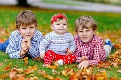 Due piccoli ragazzi felici del bambino con la ragazza di neonato, sorella sveglia Fratelli germani su erba nel parco di autunno c fotografia stock libera da diritti