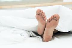 Due piedi sotto la coperta bianca Immagini Stock Libere da Diritti