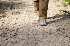 Due piedi stanno facendo un'escursione su un modo pietroso fotografie stock libere da diritti