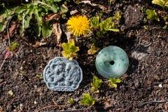 Due pietre della giada scolpite con le forme orientali su terra e su vegetazione fotografie stock