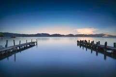 Due pilastro o molo di legno e su un refle blu di tramonto e del cielo del lago Fotografia Stock