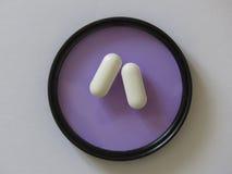 Due pillole bianche su un filtro ultravioletto Fotografia Stock Libera da Diritti