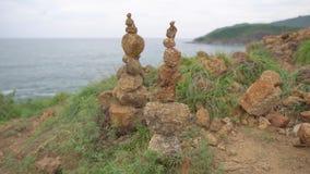 Due piramidi dei supporti delle pietre sulla terra sabbiosa Cairn sulla sommità sopra il mare stock footage