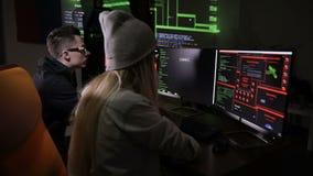 Due pirati informatici ai computer Schermi di computer con il codice su un fondo archivi video