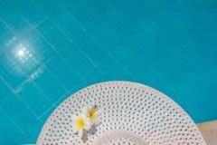 Due plumerie fioriscono sul cappello contro il contesto dello stagno Immagini Stock Libere da Diritti