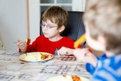 Due pochi ragazzi di scuola che mangiano la poltiglia ed il petto di pollo della patata dell'interno Immagini Stock