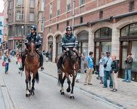 Due poliziotti montati perlustrano la via nel centro Immagine Stock