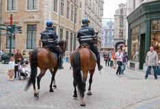 Due poliziotti montati perlustrano la via nel centro Fotografia Stock