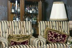 Due poltrone d'annata con le bottiglie di vecchio vino in armadietto Immagini Stock