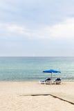 Due poltrone ed ombrelli della spiaggia Immagine Stock