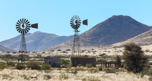 Due pompe idrauliche del mulino a vento nel calore haze sull'azienda agricola Immagine Stock