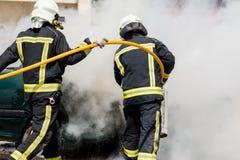 Due pompieri che mettono fuori un fuoco dell'automobile Fotografia Stock