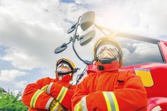 Due pompieri nel vestiario di protezione, in caschi e nella maschera contro l'autopompa antincendio che posa contro il fondo del  immagine stock
