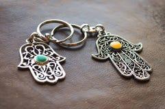 Due portachiavi a anello sotto forma di Fatima Hand su un fondo di cuoio marrone Simbolo antico e ricordo turistico moderno tradi immagine stock