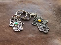 Due portachiavi a anello sotto forma di Fatima Hand su un fondo di cuoio marrone Simbolo antico e ricordo turistico moderno tradi fotografia stock