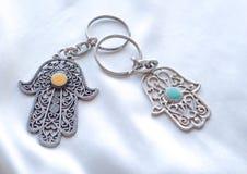 Due portachiavi a anello sotto forma di Fatima Hand su un fondo di seta bianco Simbolo antico e ricordo turistico moderno tradizi fotografie stock libere da diritti
