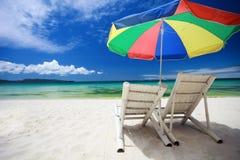 Due presidenze di spiaggia ed ombrello variopinto Fotografia Stock