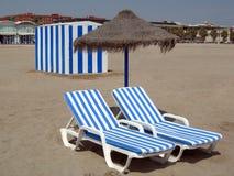 Due presidenze di spiaggia sotto l'ombrello e una cabina Fotografia Stock Libera da Diritti
