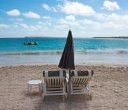 Due presidenze ed ombrelli sulla spiaggia tropicale Fotografia Stock