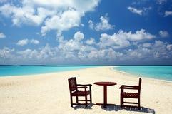 Due presidenze ed una tabella sono su una spiaggia Fotografie Stock