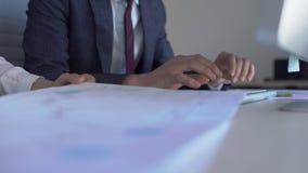 Due professionisti sono nel processo di lavoro, sedentesi allo scrittorio con il computer in ufficio moderno 4k, uomo che i tipi