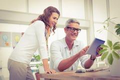 Due progettisti casuali sorridenti che lavorano con la compressa Fotografie Stock