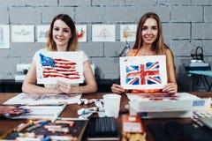 Due progettisti femminili sorridenti delle stampe che mostrano le loro bandiere americane e britanniche degli impianti, estratte  Fotografie Stock