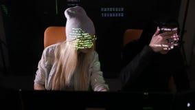 Due programmatori dell'IT, pirati informatici stanno lavorando al computer in un ufficio scuro video d archivio