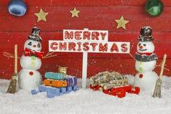 Due pupazzi di neve che tengono un segno con il Buon Natale di parole Fotografia Stock