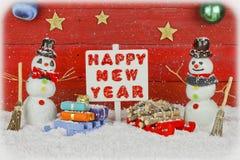 Due pupazzi di neve che tengono un signost con il buon anno di parole Fotografia Stock