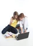 Due ragazza-allievi lavorano al computer portatile. immagini stock