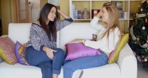Due ragazze adorabili che si siedono sullo strato e sulla conversazione Fotografie Stock Libere da Diritti
