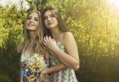 Due ragazze adorabili un soggiorno di abbraccio sulla natura immagini stock libere da diritti