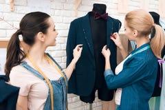 Due ragazze alla fabbrica dell'indumento che desining il nuovo uomo sono adatto al rivestimento fotografia stock libera da diritti