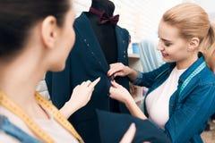 Due ragazze alla fabbrica dell'indumento che desining il nuovo uomo sono adatto al rivestimento immagine stock libera da diritti