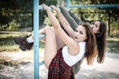 Due ragazze appendono su una barra orizzontale Il concetto degli adolescenti difficili, cattivi studenti fotografia stock