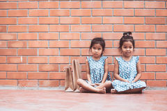 Due ragazze asiatiche del bambino che si siedono sul pavimento Immagini Stock