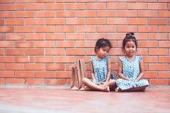 Due ragazze asiatiche del bambino che si siedono sul pavimento Fotografia Stock