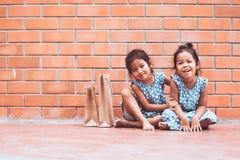 Due ragazze asiatiche del bambino che si siedono sul pavimento e che giocano insieme Immagini Stock