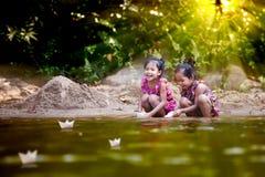 Due ragazze asiatiche del piccolo bambino che giocano barca di carta nella riva del fiume Fotografie Stock Libere da Diritti