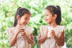 Due ragazze asiatiche sveglie del bambino che bevono insieme un latte da vetro immagini stock libere da diritti