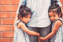 Due ragazze asiatiche tristi del bambino che abbracciano insieme la sua gamba della madre Fotografie Stock Libere da Diritti