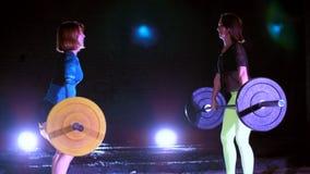 Due ragazze atletiche, atleti, alzano il bilanciere, fanno sedere-UPS con il bilanciere Alla notte, alla luce dei proiettori, den stock footage