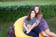 Due ragazze attraenti che si siedono accanto a ogni altro nella sedia, smilin Immagini Stock