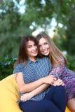 Due ragazze attraenti che si siedono accanto a ogni altro nella sedia, smilin Fotografie Stock Libere da Diritti