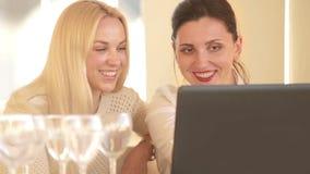 Due ragazze attraenti si siedono al computer portatile che discutono qualcosa con l'entusiasmo archivi video