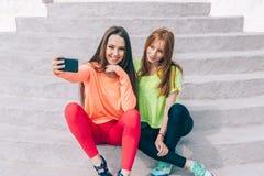 Due ragazze in attrezzature sportive fanno un selfie unito fotografia stock